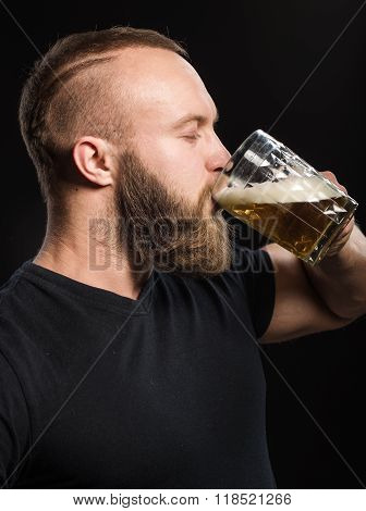 Bearded Man Drinking Beer From A Beer Mug Over Black Background.