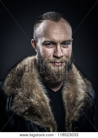 Brutal Handsome Smiling Unshaven Man With Long Beard And Moustache In Black Fur Coat With Collar.