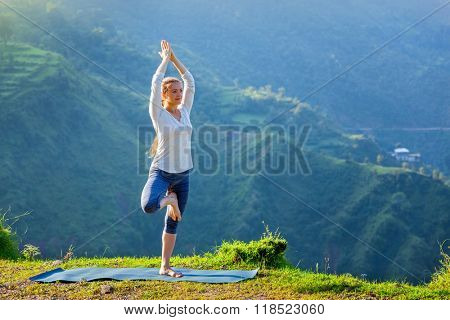 Woman practices balance yoga asana Vrikshasana tree pose in Himalayas mountains outdoors in the morning. Himachal Pradesh, India. Panorama