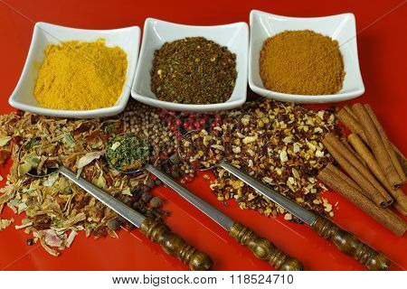 Set Of Spices And Seasonings With Old Metal Spoons On Red Table Top