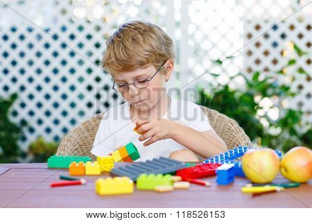 Beautiful blond child with glasses playing with lots of colorful plastic blocks indoor. Active kid boy having fun with building and creating.
