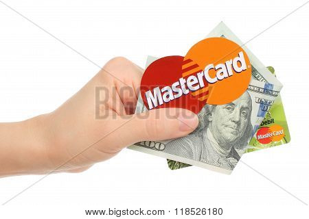 Hand holds Mastercard logo printed on paper with money and credit card on white background
