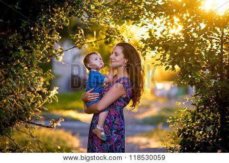 sunset mother with her son in her arms