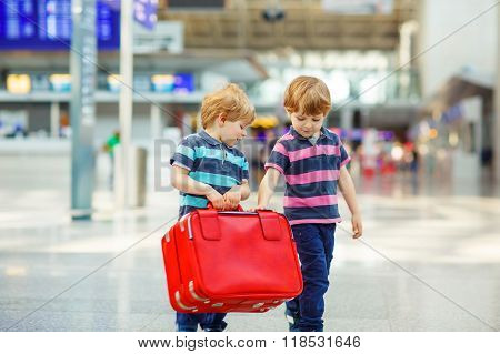 Two tired little sibling kids boys at the airport traveling together. Angry family twins children waiting. Canceled flight due to pilot strike.
