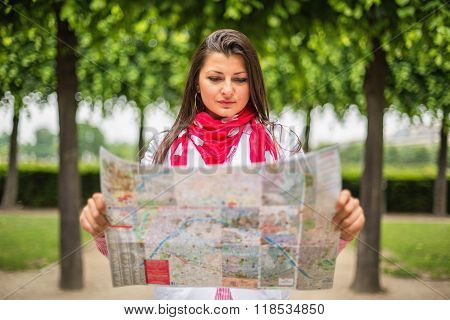 Young Woman Looking On The Map At The City Park Paris, France