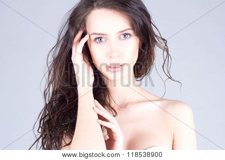 Beautiful young woman with big blue eyes and curly hair touching head. Beautiful face of woman.