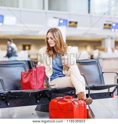 woman at international airport waiting for flight at terminal