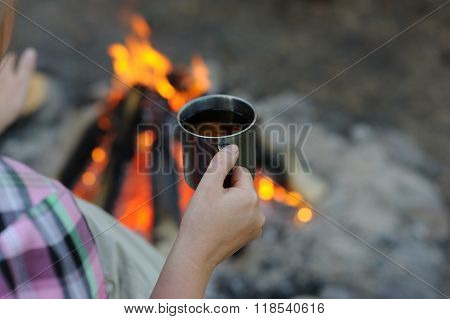 Metal Mug In The Hands Of A Tourist, In The Woods Near The Fire.
