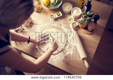 Woman preparing dough on wooden table in the kitchen.Rolled out dough with rolling pin.Pizza crust