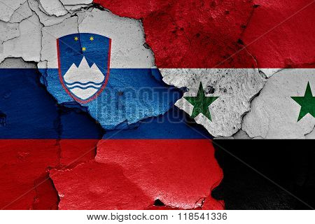 flags of Slovenia and Syria painted on cracked wall