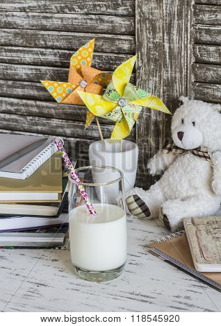 Kids Home Desk With Books, Notebooks, Journals, Handmade Paper Pinwheels And A Glass Of Milk