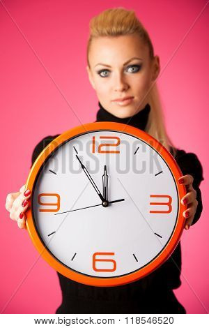 Calm Smiling Woman With Big Orange Clock Gesturing No Rush, Enough Time To Be Punctual.