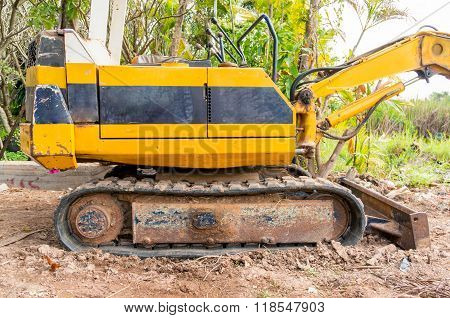 Yellow backhoe working digging in rural areas.