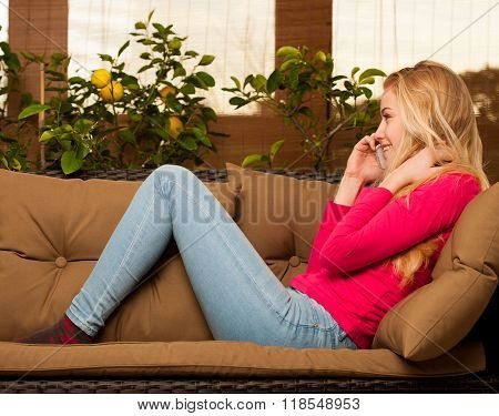 Woman Comfortable Sitting On Sofa Surrounded With Lemon Tree And Other Green Plants And Talking Over