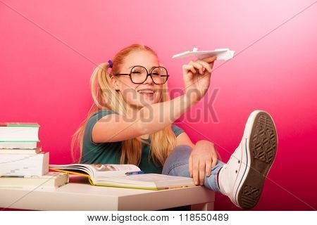 Playful, Naughty Schoolgirl With Big Eyeglasses Throwing Paper Aeroplane Sitting On Floor Behind The