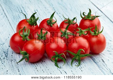 Fresh cherry tomatoes on white wooden background