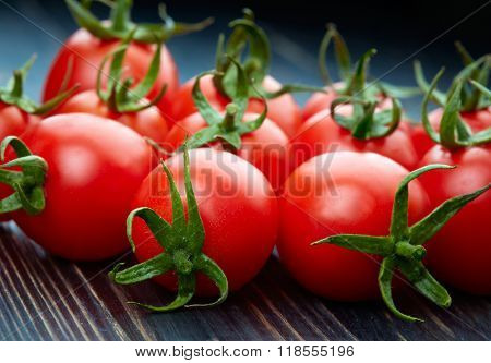 Ripe tomatoes on dark wooden background