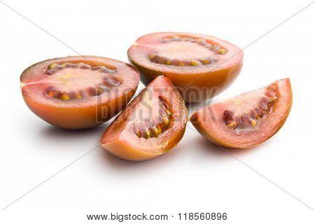 halved dark tomatoes on white background