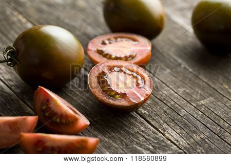 halved dark tomatoes on old wooden table