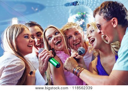 Happy friends singing karaoke at party