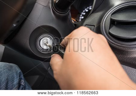 Hand Putting Car Key To The Keyhole For Starting The Car