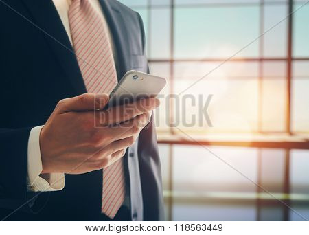 Portrait of a confident man. Entrepreneur working on phone while standing in modern office interior. Intelligent male lawyer holding phone.