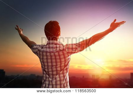 Successful man looking up to sunset sky celebrating enjoying freedom. Positive human emotion feeling life perception success, peace of mind concept. Free happy man