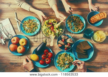 Top view of family having dinner together sitting at the rustic wooden table. Enjoying  family dinner together.