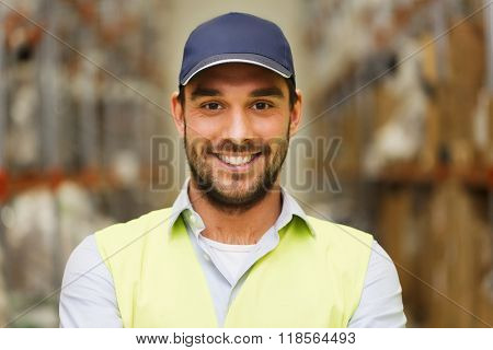 wholesale, logistic, people and export concept - happy man in cap and reflective safety vest at warehouse
