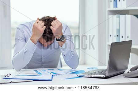 business, people, paperwork and deadline concept - stressed businessman with papers and charts sitting at table in office
