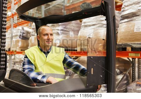 wholesale, logistic, loading, shipment and people concept - smiling man or loader operating forklift loader at warehouse