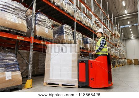 wholesale, logistic, loading, shipment and people concept - man or loader on forklift loading cargo at warehouse