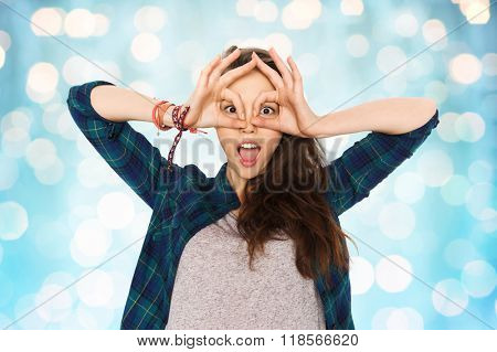 people and teens concept - happy smiling pretty teenage girl making face and having fun over blue holidays lights background