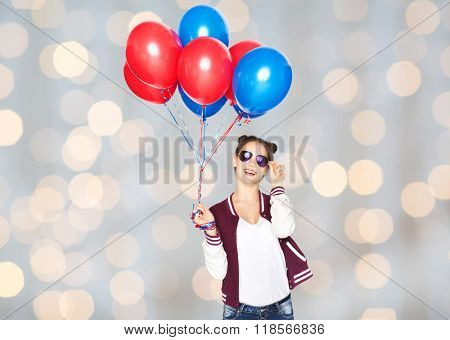 people, teens, holidays, party and summer concept - happy smiling pretty teenage girl in sunglasses with helium balloons over lights background