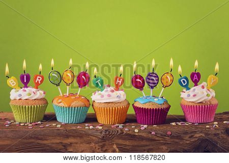 Cupcakes with candles on green background