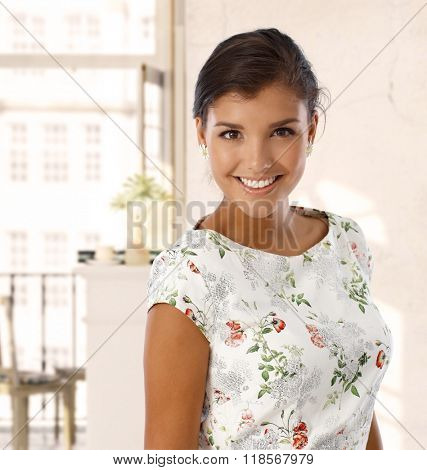 Portrait of attractive caucasian young brunette woman at vintage home. Standing, wearing colorful dress, smiling, looking at camera, toothy smile.