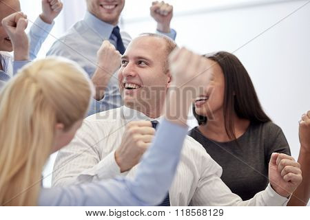business, teamwork, people and success concept - smiling business team making triumph gesture in office