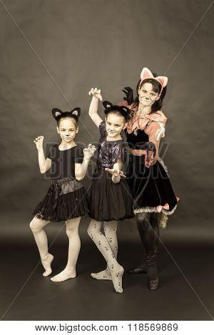 Episode Of Funny Play In Retro Style. Three Girls In Cat Costumes On Black Background.