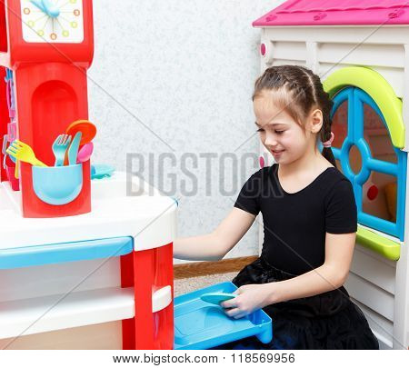 Pretty Little Girl Play Role Game With Toy Dishes At Home