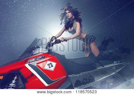 Woman posing on snowmobile