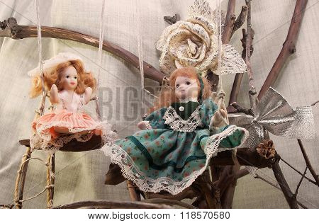 Porcelain dolls on swings photo.