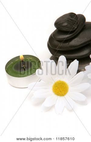 Massage stones, candle and daisy on white background