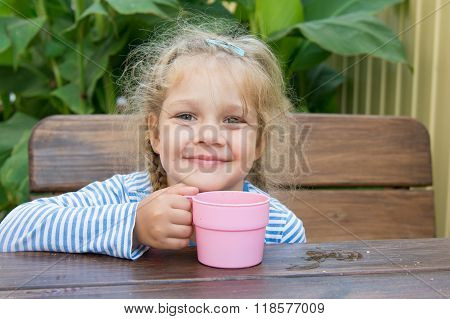 Four-year Girl Smiling While Sitting At A Table With A Glass Of Juice