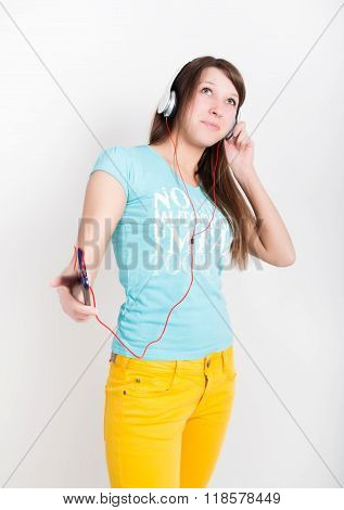 teenager girl in yellow pants, listening to music from your smartphone