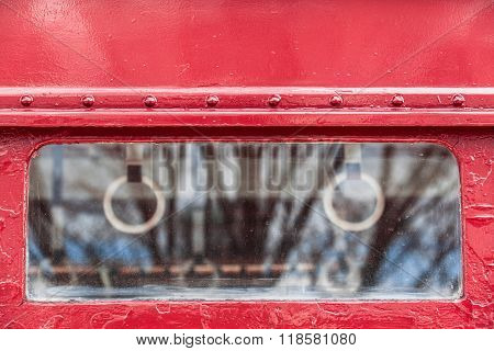 Small window of an ancient red railroad passenger car with soft details of interior like handhold grip and luggage rack
