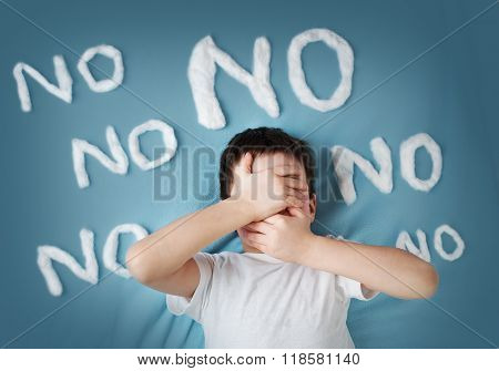 unhappy boy on blue blanket background