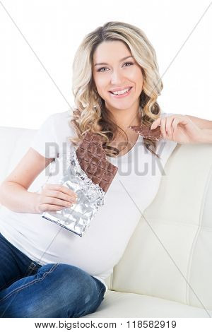 Young beautiful pregnant blond having a bite of chocolate bar.