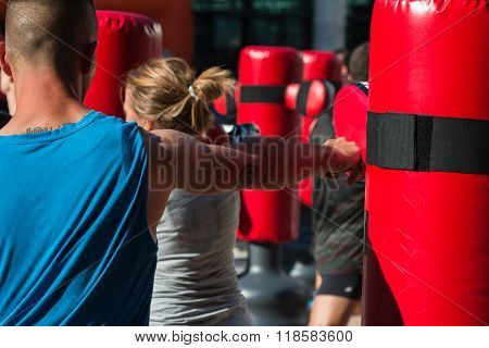 Close Up Of Young Man With Boxing Glove In Fitness Class With Red Punching Bag