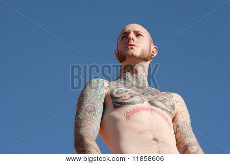 Tattoo man standing against blue sky