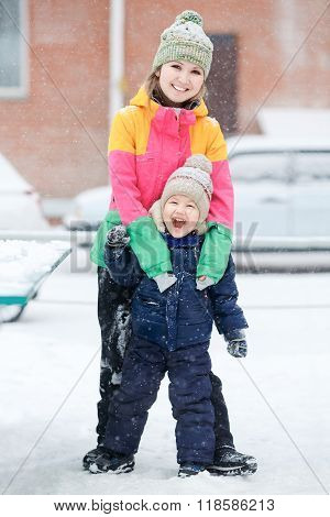 Mother with child on winter walk, positive emotions, outdoor. Snowfall, blizzard.